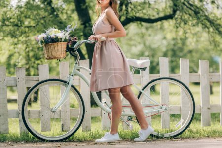 Photo for Cropped shot of stylish woman in dress with retro bicycle with wicker basket full of flowers at countryside - Royalty Free Image