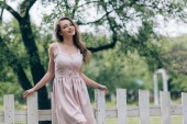 portrait of smiling beautiful woman in stylish dress standing at white fence at countryside