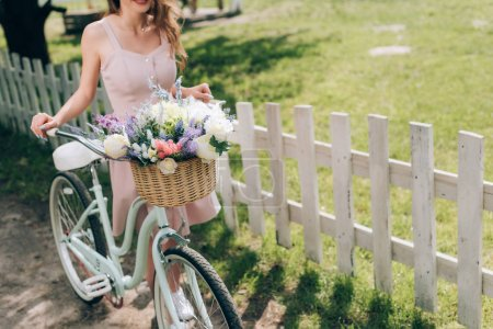 partial view of woman in stylish dress with retro bicycle with wicker basket full of flowers at countryside