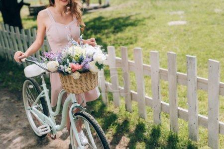 Photo pour Vue partielle de la femme en robe élégante avec vélo rétro avec panier en osier rempli de fleurs à la campagne - image libre de droit