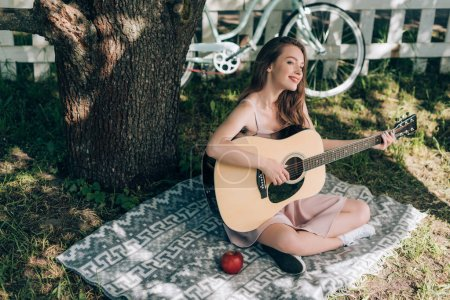 attractive young woman playing acoustic guitar while resting on blanket under tree at countryside