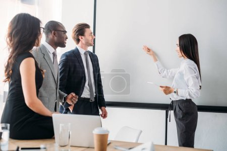 multicultural business people looking at empty white board during business meeting in office