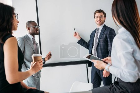 group of business coworkers in formal wear discussing new business plan in office