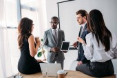 group of multiracial business coworkers in formal wear discussing new business plan in office