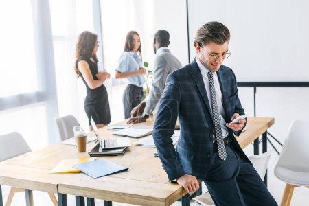 Photo pour Mise au point sélective d'homme d'affaires caucasien à l'aide de smartphone et multiraciales collègues derrière au bureau - image libre de droit