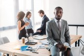 selective focus of african american businessman with coffee to go and colleagues at workplace in office