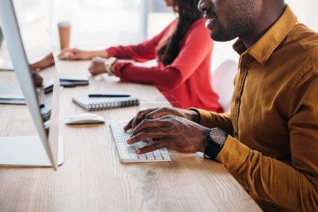 Photo pour Vue partielle des gens d'affaires afro-américains travaillant sur les lieux de travail au bureau - image libre de droit