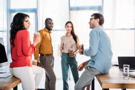 interracial business colleagues having conversation during coffee break in office
