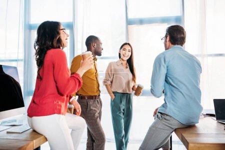 Photo pour Collègues de travail Interracial ayant la conversation au cours de la pause café au bureau - image libre de droit