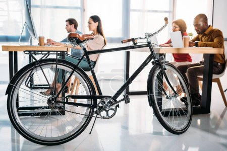 side view of bicycle and multicultural business people working in office