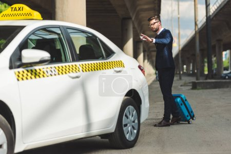 stylish young man with smartphone and suitcase looking at taxi cab