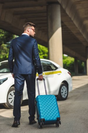 back view of stylish young businessman with suitcase standing near taxi