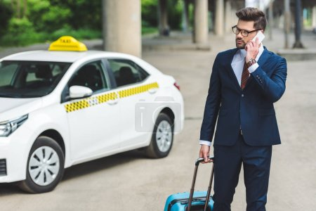 Photo for Handsome man talking by smartphone while standing with suitcase in taxi cab - Royalty Free Image