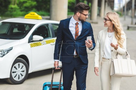 Photo for Beautiful happy young couple in formal wear smiling each other while going with suitcase near taxi - Royalty Free Image
