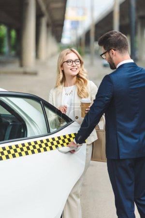 Photo pour Beau sourire café tenue fille blonde pour aller et regardant bel homme ouvrant la porte du taxi - image libre de droit