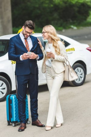 Photo for Smiling blonde woman holding coffee to go and looking at handsome man using smartphone while standing with suitcase near taxi - Royalty Free Image