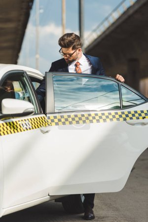 Photo for Handsome young man in fashionable suit and eyeglasses opening door of taxi cab - Royalty Free Image