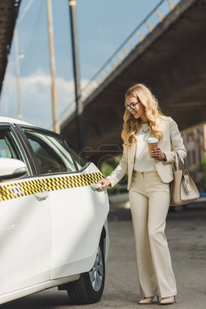 smiling blonde woman with paper cup opening door of taxi cab