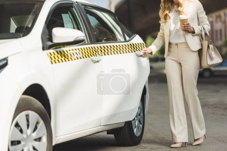 cropped shot of stylish blonde woman holding paper cup and opening door of taxi cab