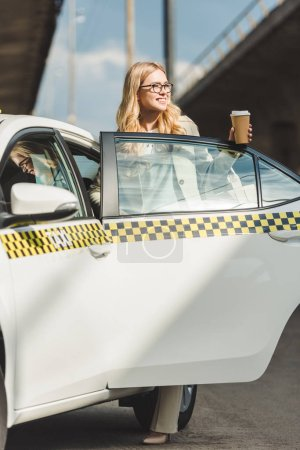 happy blonde girl in eyeglasses holding coffee to go and looking away while opening door of taxi cab
