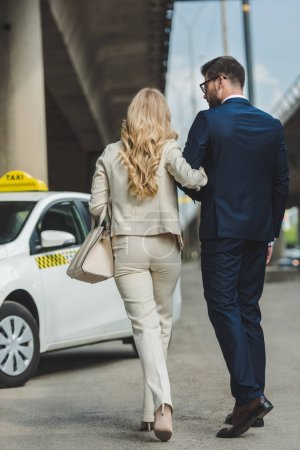 back view of stylish young couple going together to taxi cab