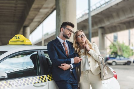 Photo for Beautiful stylish young couple in eyeglasses using smartphone and looking away while leaning together at taxi - Royalty Free Image