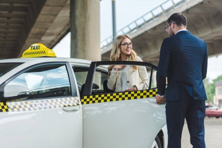 handsome stylish man opening car door to smiling blonde woman sitting in taxi