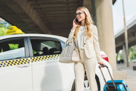 Photo for Smiling blonde woman in eyeglasses talking by smartphone and looking away while standing with suitcase near taxi cab - Royalty Free Image