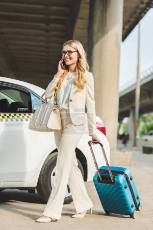 smiling blonde woman in eyeglasses talking by smartphone while going with suitcase near taxi cab