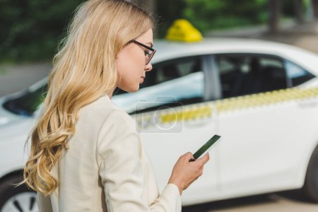 Photo for Beautiful blonde woman in eyeglasses using smartphone while standing near taxi - Royalty Free Image