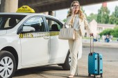 smiling blonde woman in eyeglasses talking by smartphone and looking away while standing with luggage near taxi cab