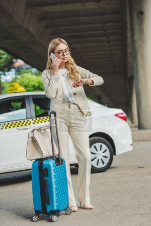 blonde woman in eyeglasses talking by smartphone and checking wristwatch while standing with luggage near taxi cab