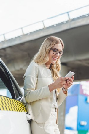 Photo for Beautiful smiling blonde woman in eyeglasses leaning at taxi cab and using smartphone - Royalty Free Image
