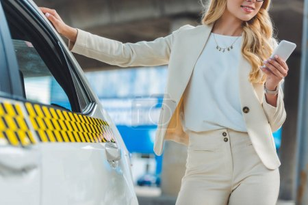 cropped shot of smiling blonde girl using smartphone while standing near taxi cab