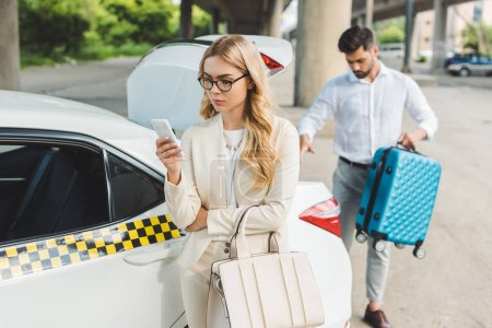 Photo for Beautiful blonde woman in eyeglasses using smartphone while man putting suitcase in trunk of taxi car - Royalty Free Image