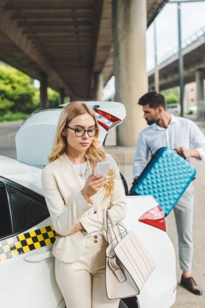 young blonde woman in eyeglasses using smartphone while man putting suitcase in trunk of taxi car