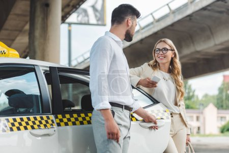 young man opening door of taxi and looking at smiling blonde woman with smartphone