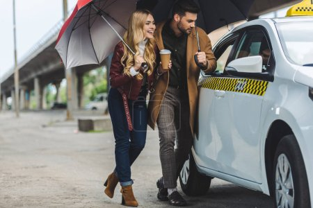 smiling young couple with umbrellas looking at taxi car