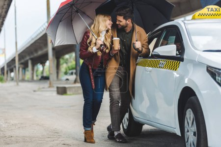 happy young couple with umbrellas smiling each other while standing near taxi cab