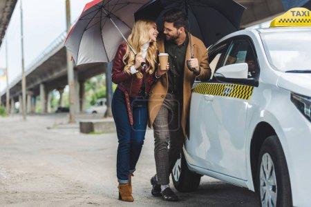 Photo pour Heureux jeune couple avec des parapluies se souriant tout en se tenant près taxi taxi - image libre de droit