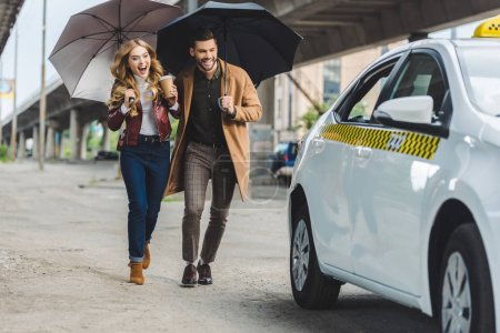 excited young couple with umbrellas running together to taxi cab