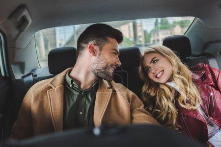 Photo pour Beau jeune couple heureux souriant mutuellement tout en étant assis ensemble dans la voiture - image libre de droit