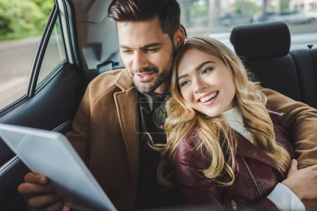 Photo for Smiling young couple using digital tablet while sitting together in car - Royalty Free Image