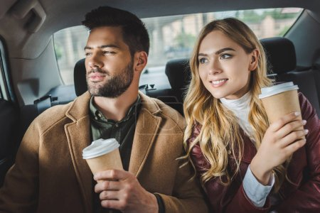 smiling stylish young couple with paper cups sitting together in taxi