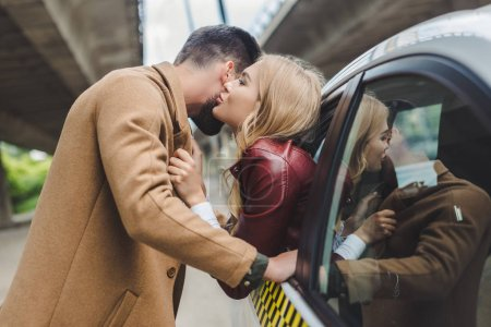 side view of young couple kissing, girl sitting in taxi and man standing on street