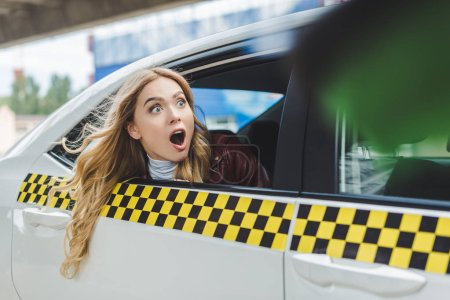 selective focus of shocked girl looking away through taxi window