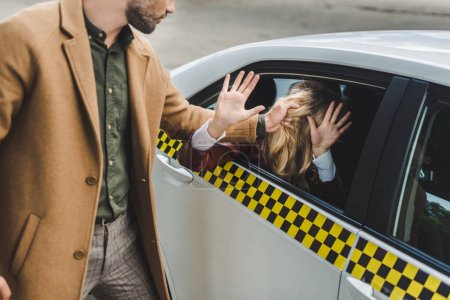 cropped shot of man holding hair of young woman sitting in taxi