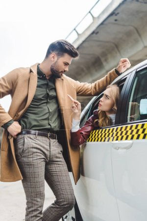 serious young woman sitting in taxi and pointing with finger at man leaning at car