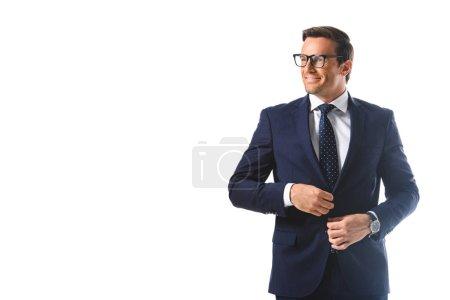 happy businessman in eyeglasses adjusting jacket isolated on white background