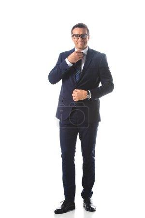 heureux homme d'affaires en lunettes de vue réglage cravate isolé sur fond blanc